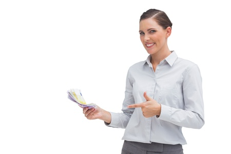 Happy businesswoman pointing to money in her hand on white background Stock Photo - 20539199