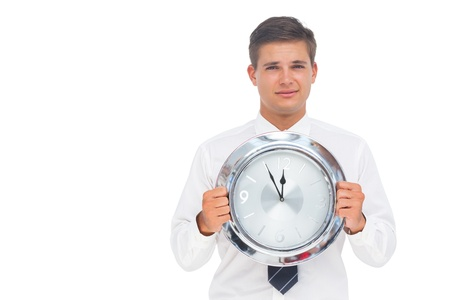 Nervous businessman holding a clock on white background photo