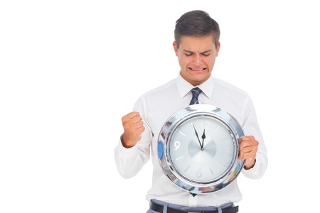 Anxious businessman holding and looking at clock on white background photo