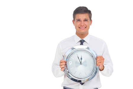 Concerned businessman holding clock on white background photo