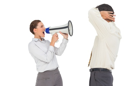 Businesswoman shouting at businessman with megaphone on white background photo