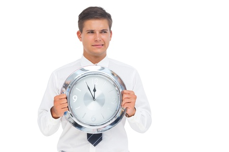 Anxious businessman holding a clock on white background photo