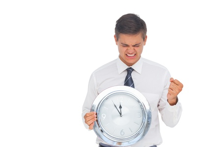 late twenties: Excited businessman holding a clock on white background
