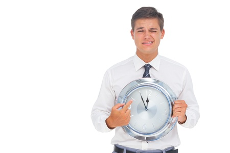 Worried businessman holding and pointing at clock on white background photo