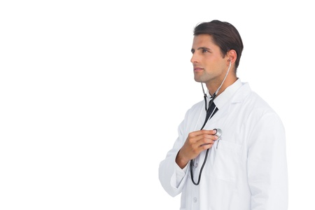 Seus doctor holding up stethoscope to his chest on white background Stock Photo - 20516650