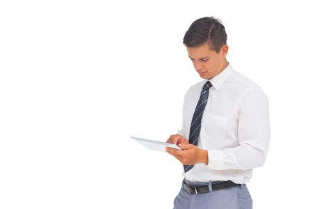 Frowning businessman using tablet on white background photo
