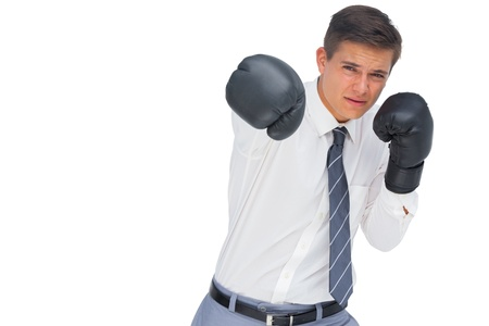Businessman punching with black boxing gloves on white background photo