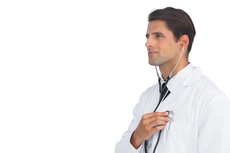 Smiling doctor holding up stethoscope to his chest on white background Stock Photo - 20539205