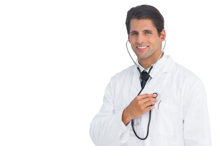 Happy doctor holding up stethoscope to his chest on white background Stock Photo - 20539209