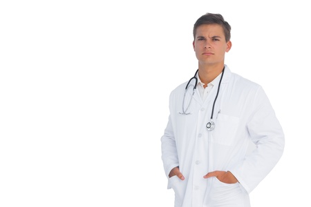Doctor frowning with hands in pockets on white background Stock Photo