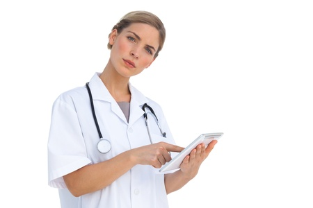 Serious nurse pointing something on tablet pc on white background photo