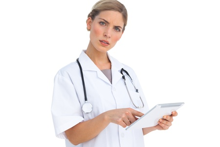 Annoyed nurse using tablet pc on white background photo