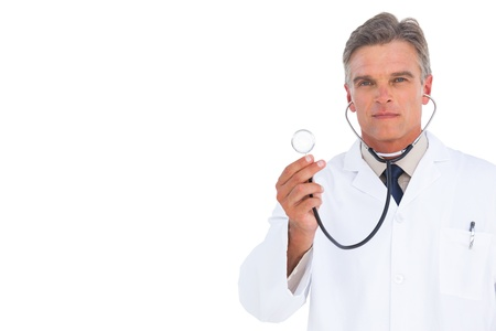 Serious doctor holding stethoscope on white background Stock Photo - 20539210