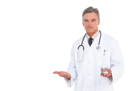 Serious doctor holding drugs and water glass looking at the camera photo