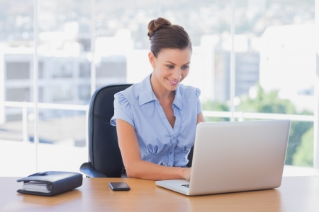 desk work: Happy businesswoman working on her laptop in the office