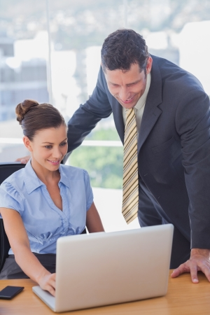 Business people working together on a laptop and smiling in the office Stock Photo - 20517861