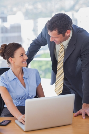 Happy business people smiling and working together with a laptop in the office Stock Photo - 20591941