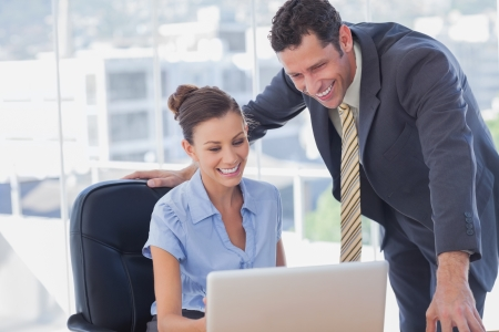 Smiling business people working together with the same laptop in the office Stock Photo - 20591805