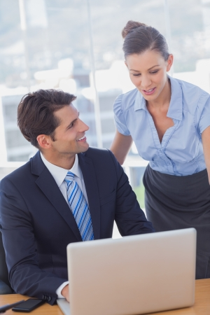 Happy business people working together with a laptop and smiling in the office Stock Photo - 20591604