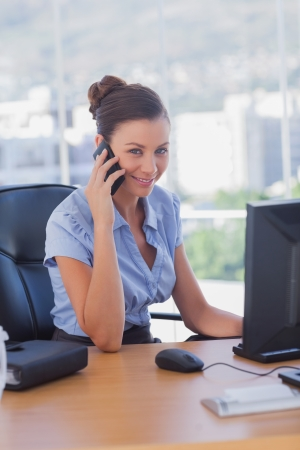 Happy businesswoman on the phone in her office photo