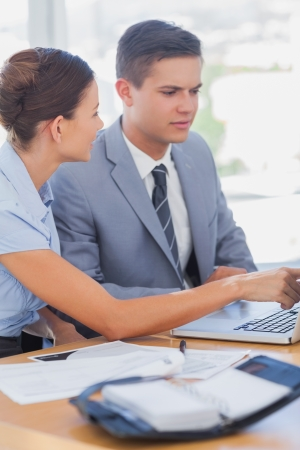 Smiling businesswoman showing partner something on a laptop in the office  photo