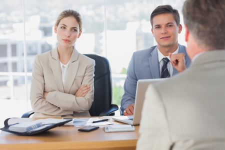 Happy business people interviewing business man in the office  photo
