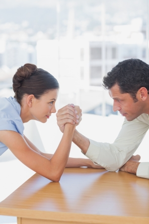 competitive business: Competitive business people arm wrestling in the office Stock Photo