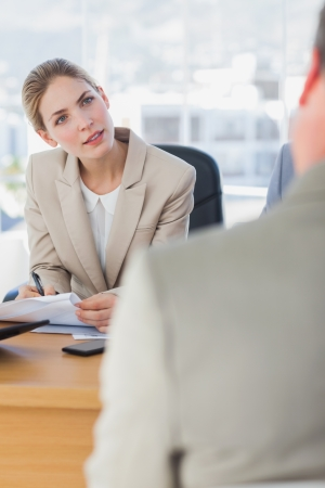 Smiling businesswoman looking at interviewee in the office  photo