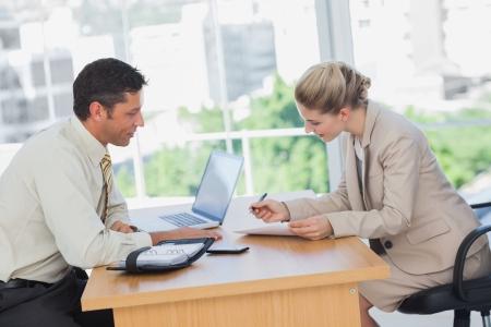 firmando: Empresaria que firma contrato en la entrevista en la oficina