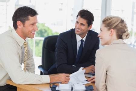 business communication: Business people smiling during a meeting in the office