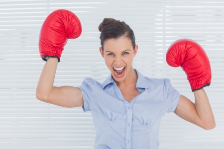 empowered: Businesswoman in boxing gloves cheering in the office