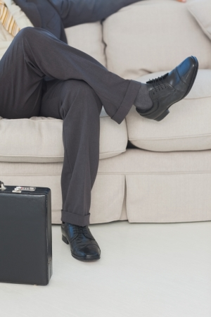 Businessman with legs crossed on couch in office photo