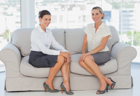 Happy business women sitting on the couch smiling at camera photo