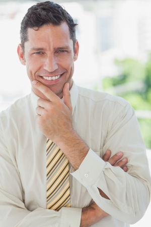 Businessman smiling with hand on chin in office photo