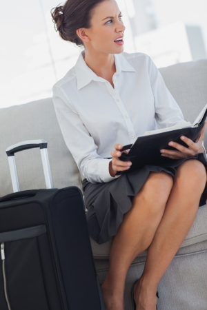 Angry businesswoman with diary and suitcase on couch