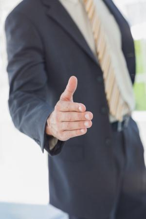 extending: Businessman extending arm for handshake in office