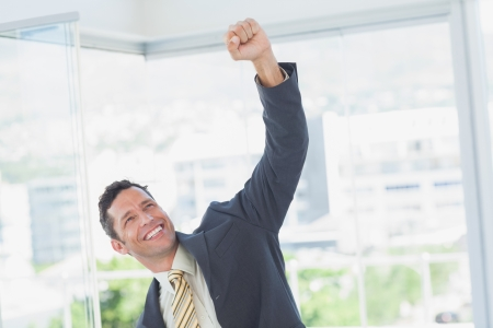 acclamation: Cheerful businessman raising up his hand in office