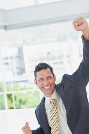 Businessman cheering in office photo