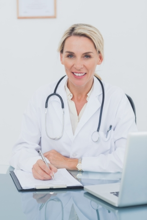 Portrait of an attractive doctor posing in her office while writing on a clipboard photo