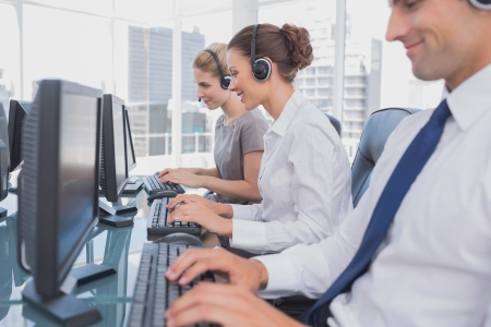 service center: Call centre employees at work on computer in office