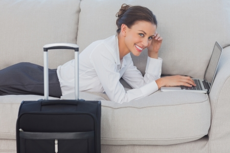 Business woman lying on couch and looking at camera using laptop photo