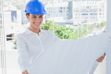 Cheerful architect rolling out a blueprint and wearing a hardhat in a modern office photo