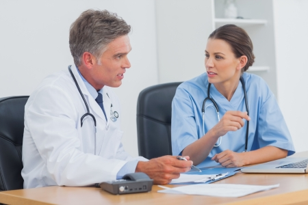 diagnosing: Two doctors discussing and working together in a medical office