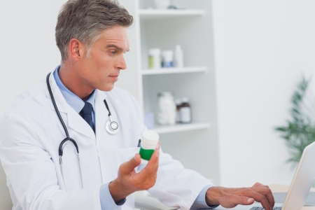 doctor holding pills: Serious doctor holding pills and using laptop