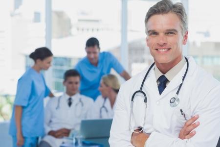Office uniforms: Doctor hermoso con los brazos cruzados de pie en frente de un equipo m�dico
