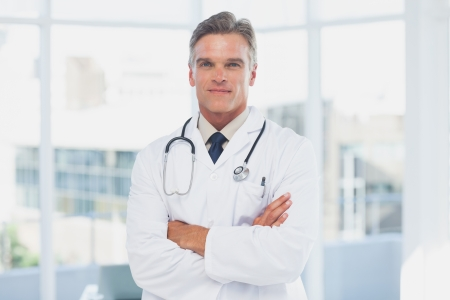 grey haired: Grey haired doctor with arms crossed Stock Photo