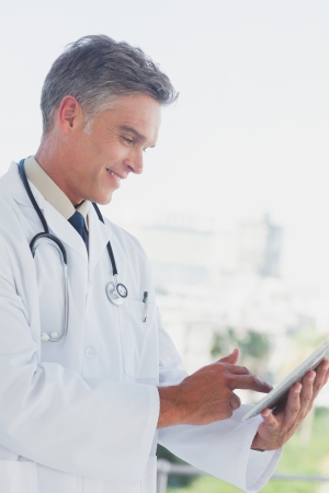 grey haired: Grey haired doctor using digital tablet in a bright office