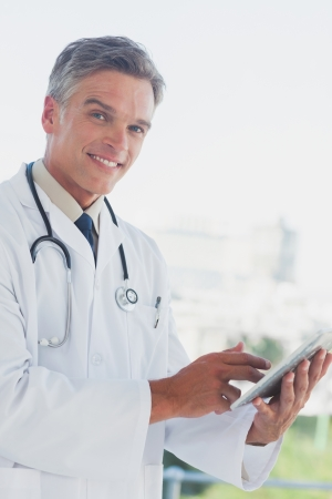 grey haired: Grey haired doctor smiling and using digital tablet in a bright office