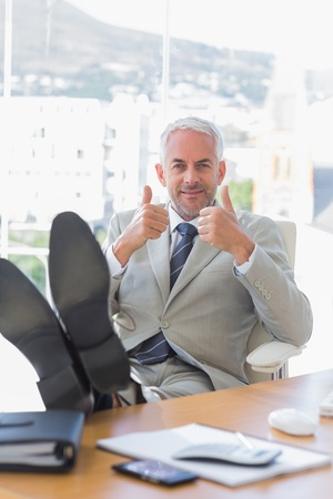 Happy businessman giving thumbs up with feet up on his desk Stock Photo - 20500652