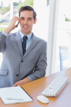 Smiling businessman on the phone looking at camera at his desk Stock Photo - 20591641